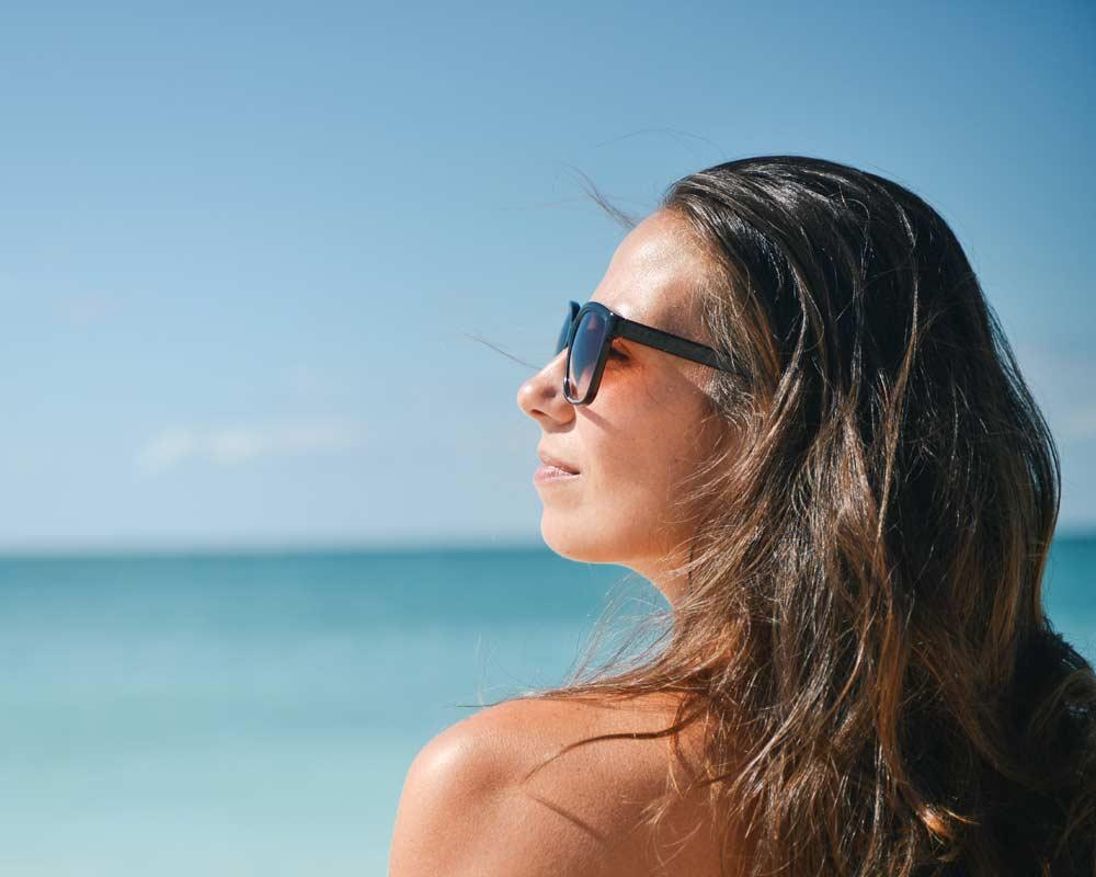 CareAcross-skin-cancer-melanoma-woman-beach-sunglasses